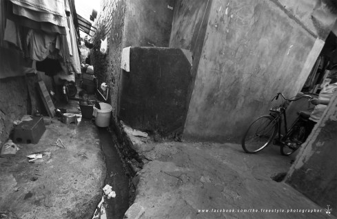 Venturing into the slum area of Jakarta, a boy was bathing by the drain while cyclists/motorcyclists squeeze through the narrow alley.