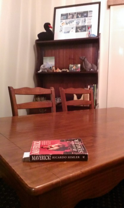 A table with two matching chairs and a book (Maverick, by Ricardo Semler) on top
