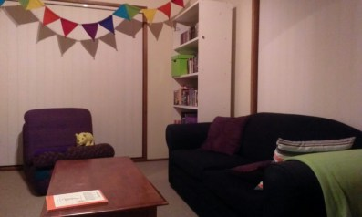 The right half of a lounge room with bright furniture and decorations
