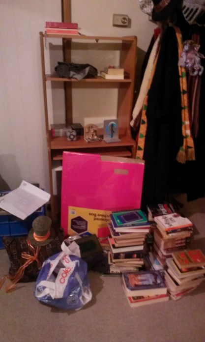 A messy area with lots of stacked books and packing equipment
