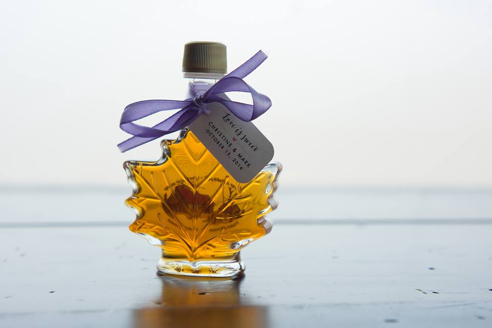 A small bottle of maple syrup in the shape of a maple leaf.