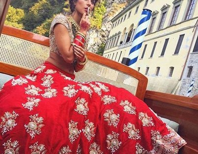 Light Red lehenga with spaced out big floral motifs in Gold Zari paired with a dull gold heavy blouse | Curated by Witty Vows
