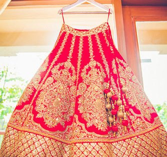 Beautiful Red lehenga hanging on a hanger with gold gotta patti work | Big motifs along the kali and broad gotapatti border | Asiana Couture | Curated by Witty Vows