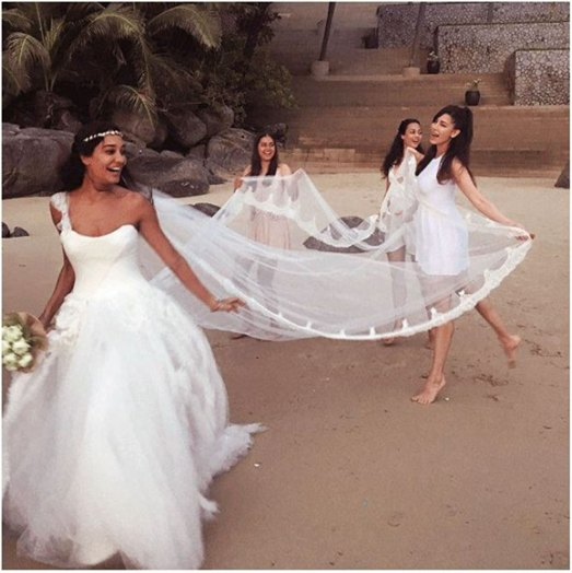 Indian Wedding trends 2016 for a perfect Indian Bridal look | lisa hayden in a pretty white christian wedding dress with a train held by her sisters, friends and nieces - trend on point!