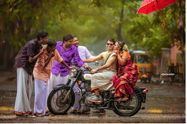 Indian bride and groom on a bike with her brothers stopping them