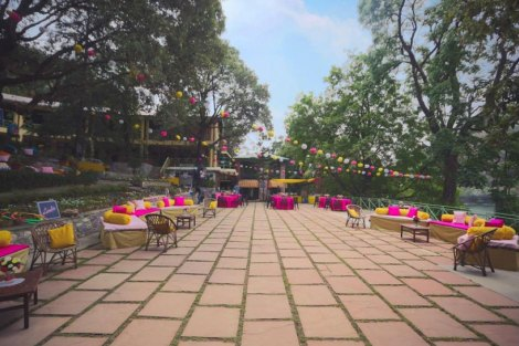 A fun and playful colourful hill station wedding in nakauchiatal | Daytime mehendi | yellow and pink | Lakeside wedding inspiration | colourful outdoors Indian Mehendi decor |Pom Pom paper decor | Jonathan & Subhashree | Curated by Witty Vows