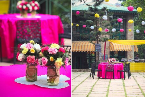 Pink Mehendi round table linen decor with mason jars and colourful flowers with cut lemon and orange slices under the paper pom poms   Jonathan & Subhashree   Curated by Witty Vows   Indian Mehendi decor ideas