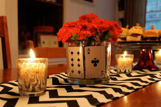 Use playing cards in a simple round glass vase with red roses to create a pretty centrepiece idea for your first diwali cards party