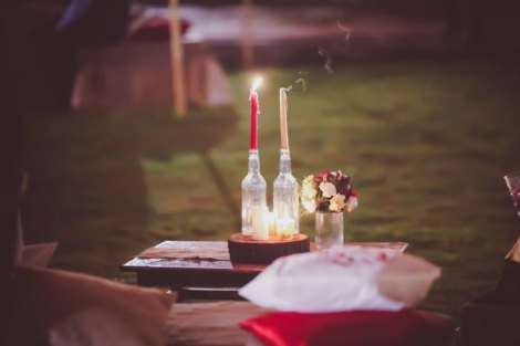 Tall candles in glass bottles upon wooden logs for decor | decor ideas for a cozy and intimate garden party | rustic chic Indian destination wedding Ideas | Christian ceremony by Indian couple | Outdoor decor ideas for Indian wedding | Chandelier alter with red drapes from trees and the aisle lined with baby breath | Subhashree and jonathan | Woodland wedding in the hills | Budget bride | Curated by Witty Vows