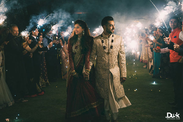 Groom and Bride exit ideas for Indian Weddings | vadai ideas | wedding send off ideas | couple exit ideas | Groom in creme sherwani with bride in red lehenga | Indian couple with sparklers | Sparkler exit for wedding