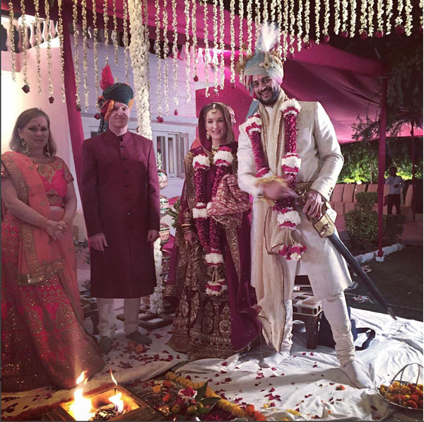Actor Arunoday Singh's Wedding in Bhopal with lee Elton | Groom with a creme sherwani and multicolour Saafa | Bride in a maroon and gold lehenga with a thick red and white rose spiral jaimala