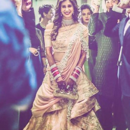Indian Wedding Ideas from Suyyash and Kishwer's Wedding Reception | Kishtwar in a peach & silver lehenga and suyyash in a white tux | peach of shoulder lehenga with pearl detailing