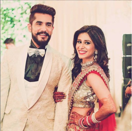Indian Wedding Ideas from Suyyash and Kishwer's Wedding Reception | Kishwer in red lehenga with a gold blouse and detailing in mirror & Suyyash in a white tux | we decide on forever backdrop with letters white on green grass backdrop