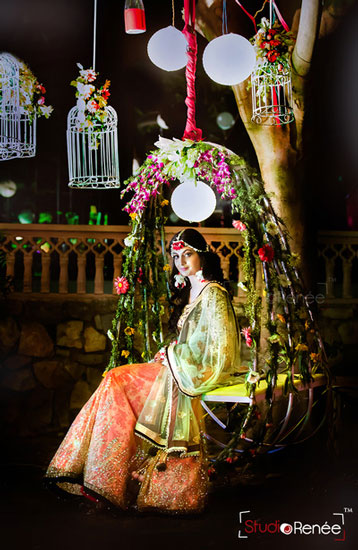 Mehndi jhoola and innovative mehndi decor ideas | beautiful mehndi swing bridal seat idea Cane garden swing decorated in carnation flowers with bird cages Photo by - Studio Renee