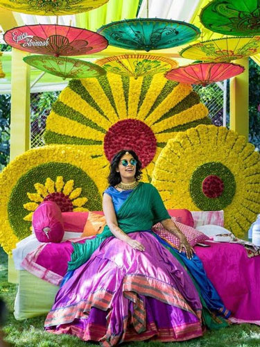 innovative mehndi decor ideas | beautiful mehndi Bridal seat sofa with pretty pin wheel inspired green and yellow flower studding backdrop decor and pink and green sofa lounger for bride | Photo by - Epics by Avinash