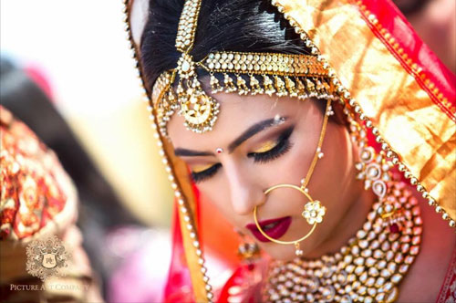 Top Indian Bridal Makeup trends | Makeup for bride | Getting ready photo | wedding look - Gold and red smokey eyes with deep red lipstick | Pretty Kundan mathapatti and Nath | Makeup idea | Photo by - Picture Art Company