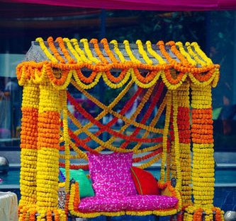Mehndi jhoola and innovative mehndi decor ideas | beautiful mehndi swing bridal seat idea with bride on marble swing set dressed in marigold Photo by - Dot Dusk
