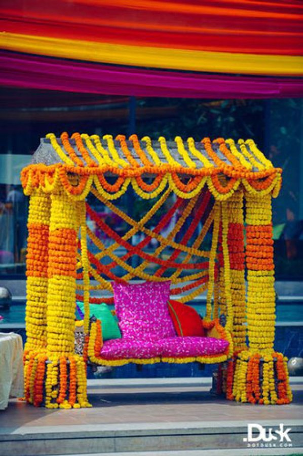 Mehndi jhoola and innovative mehndi decor ideas | beautiful mehndi swing bridal seat idea with bride on marble swing set dressed in marigold Photo by - Dot Dusk