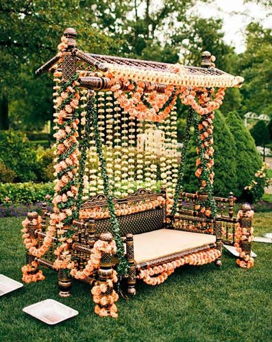 Mehndi jhoola and innovative mehndi decor ideas | beautiful mehndi swing bridal seat idea traditional carved swing decorated in pastel carnation flowers Photo by - Collin Cowie Weddings