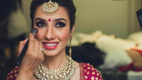 Top Indian Bridal Makeup trends | Makeup for bride | Getting ready photo | wedding look - pink lipstick and magenta bindi | Makeup idea | Photo by - Tuhina Chopra Photoworks | Pretty Indian bride wearing a magenta and gold blouse with kurgan tika