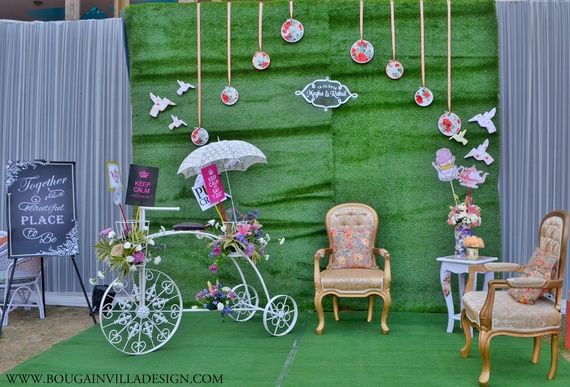 photo open a parisian vintage style | Green backdrop with birds plates lace umbrellas and a pretty vintage armchair | Indian wedding photoshoot ideas | Indian bride in pretty pink gown | Indian wedding photo booth ideas | Photo Op ideas | fun wedding photos | bougainvillea design