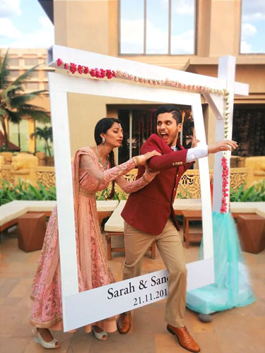 photo op Indian groom running caught by the bride in an Instagram frame | Indian wedding photoshoot ideas | Indian bride in pretty pink gown | Indian wedding photo booth ideas | Photo Op ideas | fun wedding photos