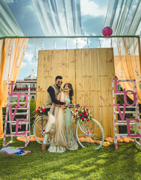 photo op A rustic backdrop with cages flowers and photo frames with a pretty decorated white bicycle | Loe alphabets in pink on ladders | Indian wedding photoshoot ideas | Indian bride in pretty pink gown | Indian wedding photo booth ideas | Photo Op ideas | fun wedding photos | Shutter down
