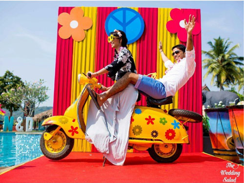 photo op with a colourful yellow scooter with flowers | Indian wedding photoshoot ideas | Indian bride in pretty pink gown | Indian wedding photo booth ideas | Photo Op ideas | fun wedding photos | The wedding Salad