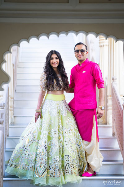 Coordinated outfits, Tips for Couple outfits | Bride wearing a light green and silver lehenga and groom wearing a bright fuschia pink salwar kurta with waistcoat | photo - stories by Joseph Radhik | matching the outfits the right way