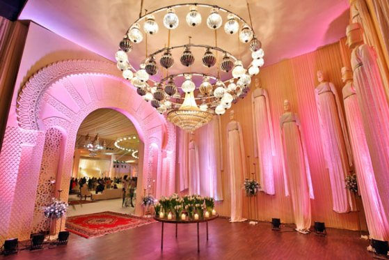Ridhi Mehra's reception space with ivory fabric drapes, Moroccan lamps in gold and large puppets