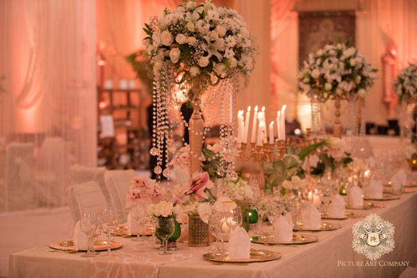 white rose and lily centrepieces with gold candle bras and crystals