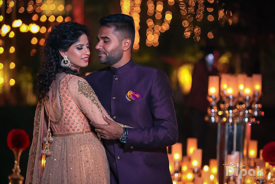 Sukriti and amrits glam delhi wedding | bride in peach Anarkali and groom in a blue suit with a red pocketsqaure