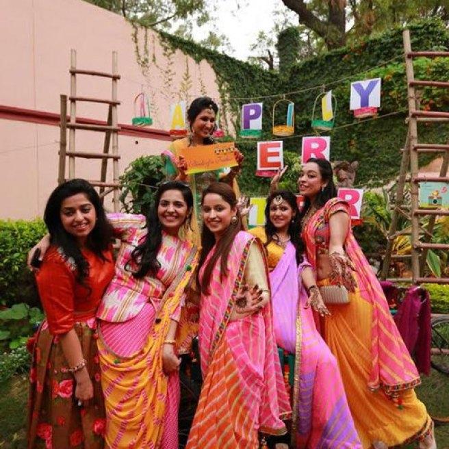 Indian bridesmaids in matching lehariya sarees at the photo booth