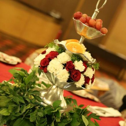 tall wedding centrepiece with tiers of flowers in itawah stands with fruits