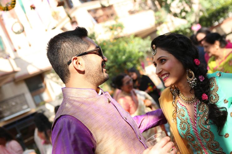 Delhi wedding ideas Karan & Sangini | Groom wearing purple kurta and waistcoat and bride wearing a turquoise gottapatti kurta with a pink lehariya sharara | Kundan bold and chained earrings with small flowers in her braid hair