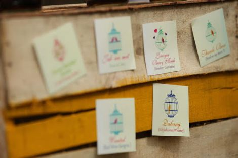 Quirky cartons used as menus with custom drink names for mehndi decor