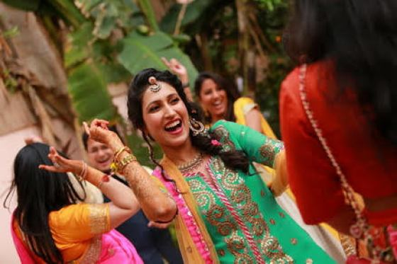 Indian bride dancing at her Mehndi in gotapatti turquoise kurta and leheariya sharara with flowers in her hair