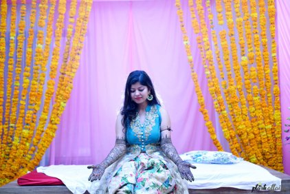 Indian bride in a floral lehenga for her mehendi | Mehndi happy bride | green and ivory floral lehenga | Divya and Nikhil | Mehndi bed with marigold strings as decor