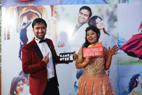 plush affairs photography | Peach gown for the Indian bride with flowers and shimmer | maroon and black tux suit for the Indian groom with a black bow tie | couple holding signs at the photo booth