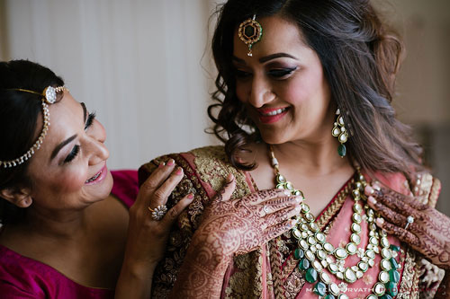 Indian bride getting ready for her wedding mother doing finishing touches