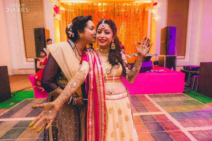 Indian brides mother kissing her daughter at her mehndi