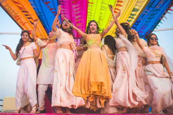 Masoom Minawala holi party | indian bride with bridesmaid | colourful Indian party tent | Indian bride Masoom minawala wearing yellow beige plain lehenga | happy Indian bride | Indian blogger's wedding | Indian wedding trends