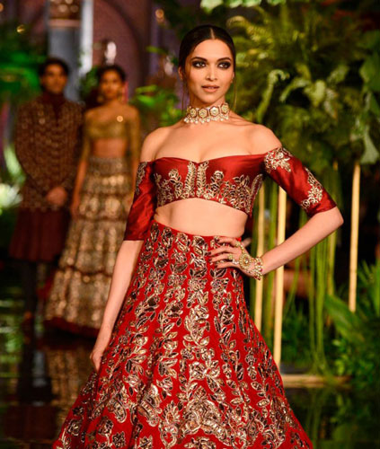 Latest blouse styles   new blouse styles to love   latest blouse designs for Indian brides   Indian bride with beautiful twisted braid with baby's breath flowers   Deepika Padukone in an off shoulder red and gold manish Malhotra outfit   off shoulder blouse for brides
