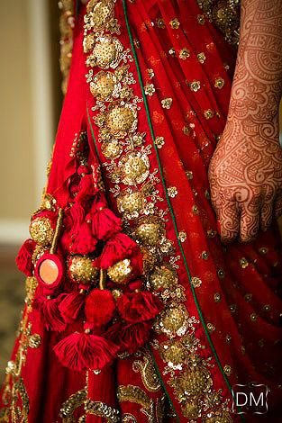 lehenga latkan ideas to spruce up your wedding lehenga | personalised latkans in different shape | Red and gold sequin pom pom and tassle latkans