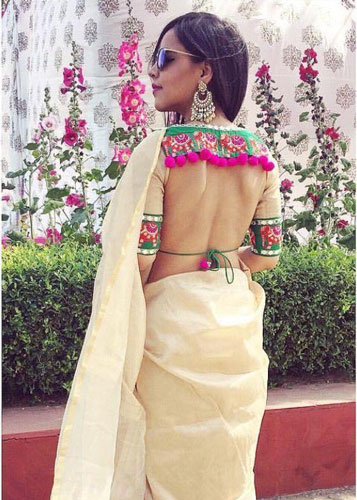 Latest blouse styles   new blouse styles to love   latest blouse designs for Indian brides   Indian bride with beautiful twisted braid with baby's breath flowers   Open back cut out style blouse with colourful pom poms sexy blouse styles
