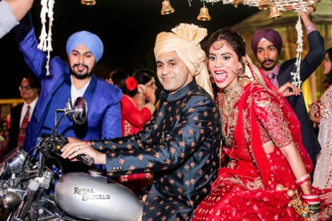 JyotPriya and Nishant | Punjabi wedding in Delhi | The bride's cool wedding entry on a Royal Enfield with her brother.