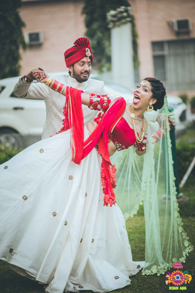 Chitrakshi and Neil | Offbeat wedding in Delhi | Day wedding full of ideas | Indian bride wearing an ivory lehenga with a floral sleeve blouse and a red and pista pastel double dupatta | Indian bride with a red sweetheart blouse with red white and green 3d flower decoupage on the sleeves |  Indian bride and groom drinking beer together | photo by Design Aqua | WIttyVows | super fun candid couple | funny faces