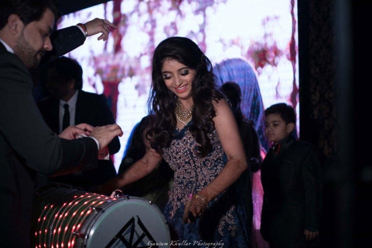 Indian bride play9ing the dhol at her sangeet