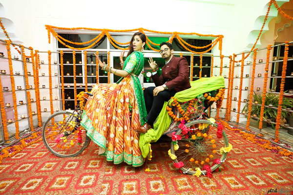 JyotPriya and Nishant | Punjabi wedding in Delhi | The bride and groom posing on the flower studded colorful rickshaw with beautiful decor in the background looked so awesome.