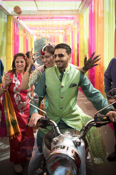 Anukriti and Siddharth | Delhi Wedding full of simple nd fun wedding ideas | Photo by AnImage Productions | Indian couple on a bike | Bride enters behind the groom on a bike with her mehndi on and floral jewellery | groom in green waistcoat and blue shirt